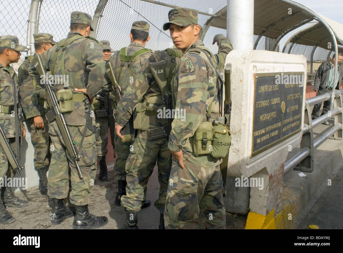A small group of Mexican army soldiers walks along the Santa Fe Bridge between Ciudad Juarez and El Paso Texas Stock Photo