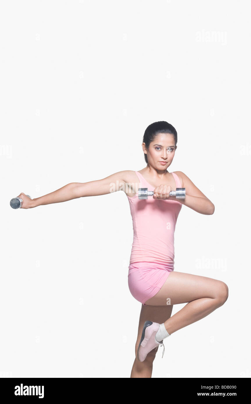 Portrait of a young woman exercising with a pair of dumbbells Stock Photo