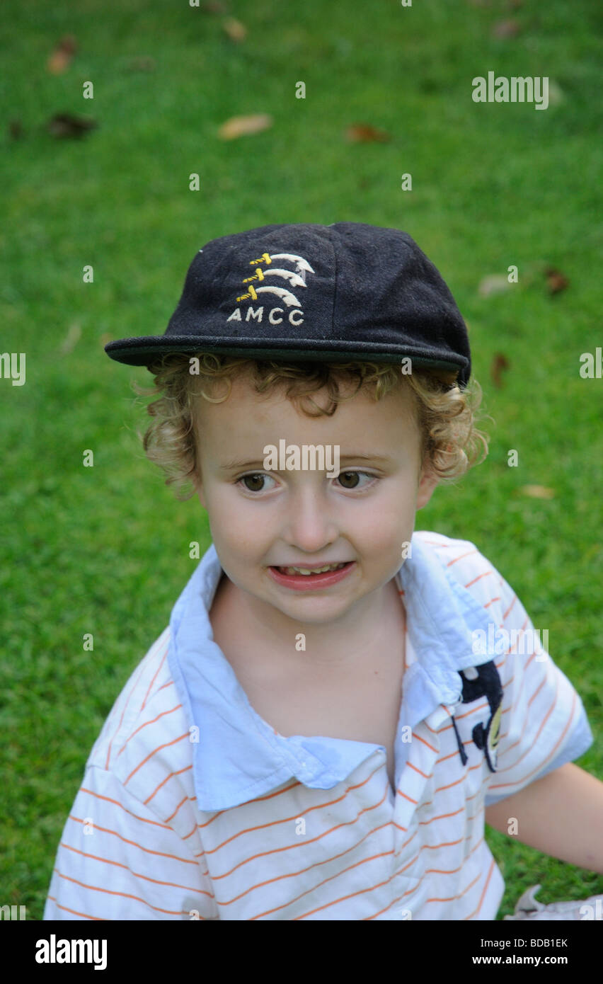 2cfd916e Little boy dressing up and wearing a AMCC cricket cap - Stock Image