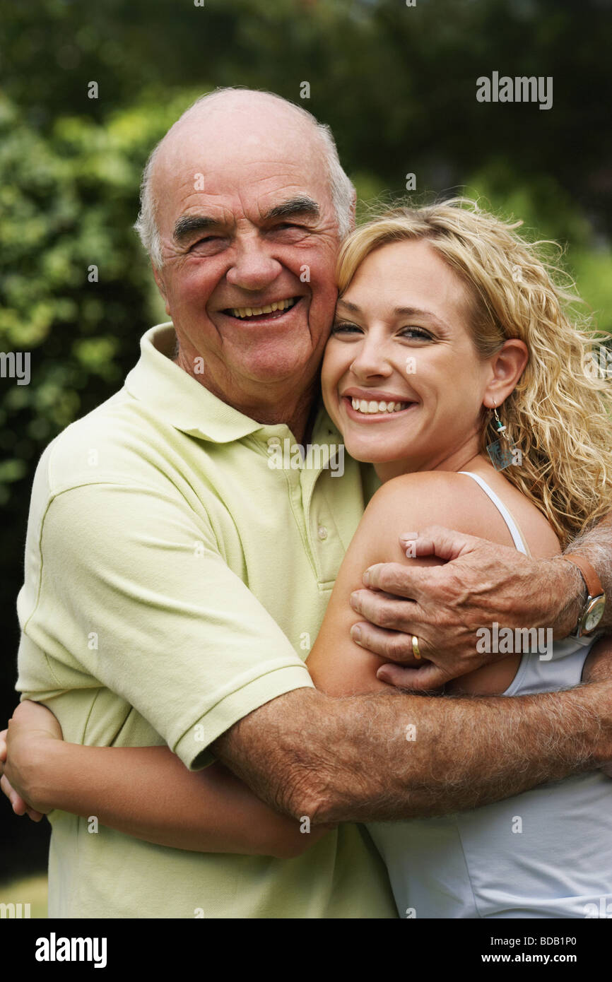 Portrait of a senior man smiling with his granddaughter - Stock Image