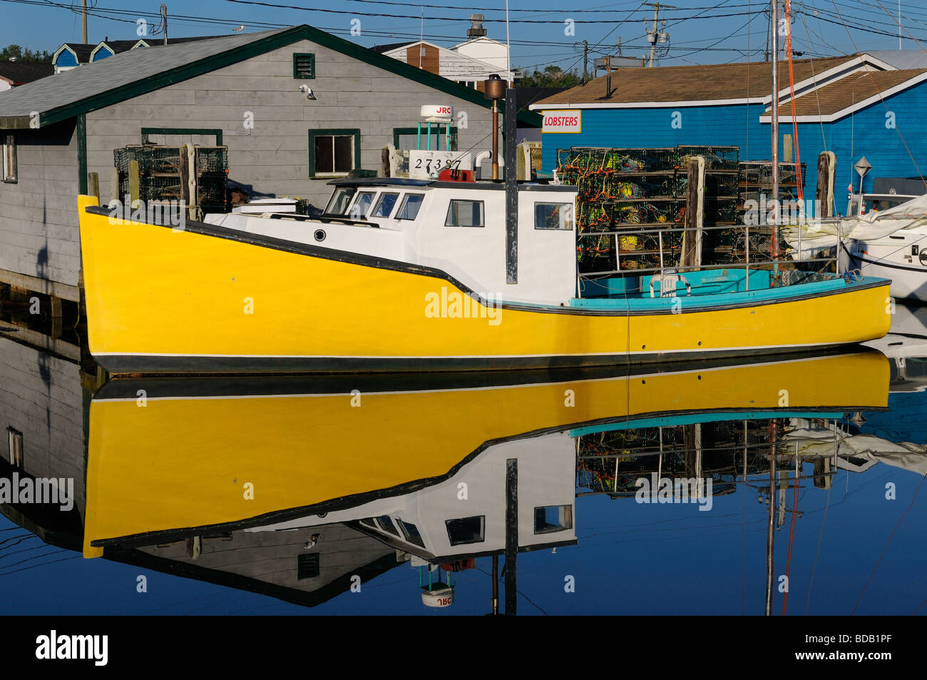 Yellow lobster boat on calm blue water at Fishermans Cove Eastern Passage Halifax Nova Scotia - Stock Image