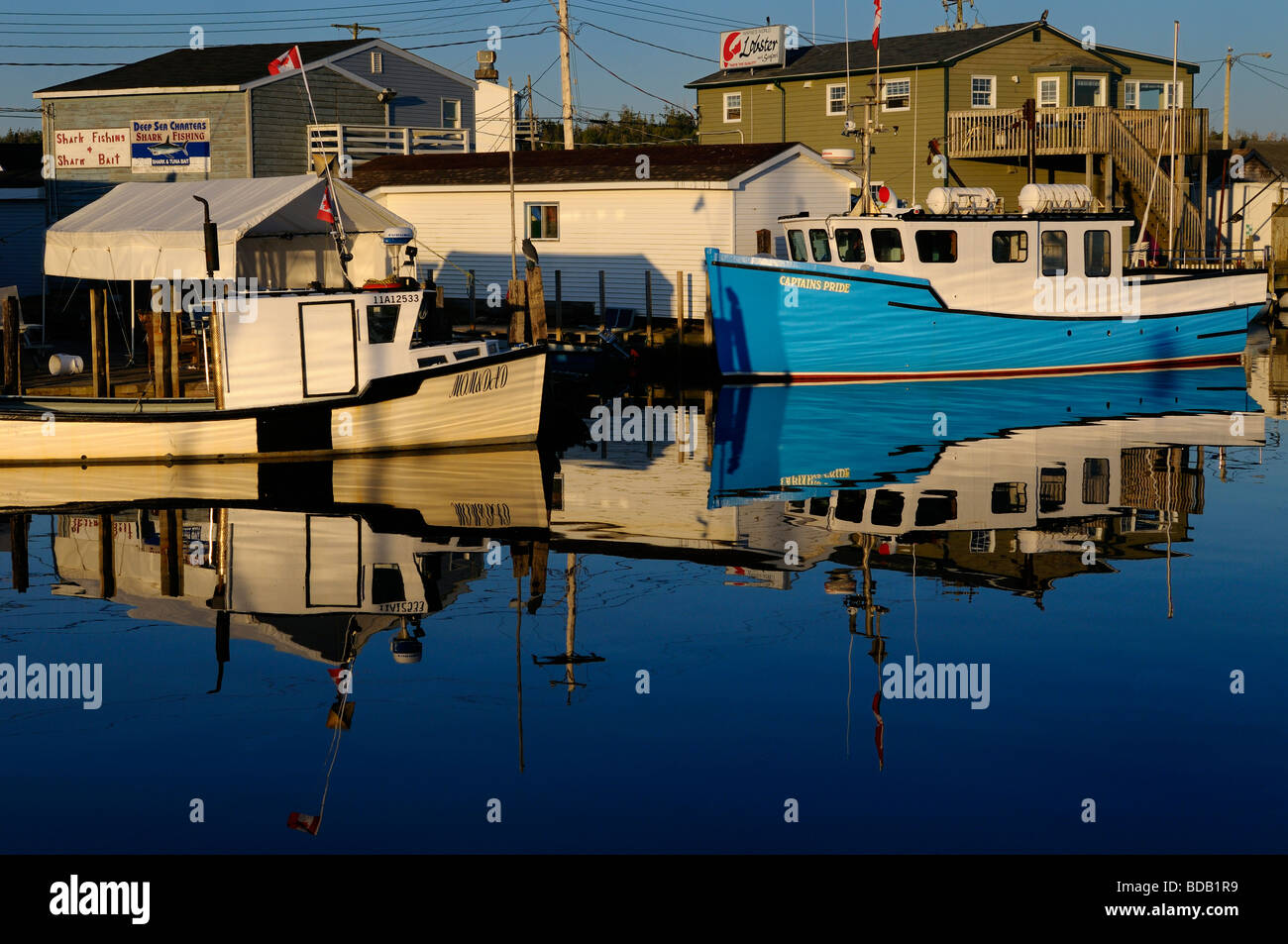 Deep sea shark charter boats on calm morning water on blue sky day at Fishermans Cove Eastern Passage Halifax Nova - Stock Image