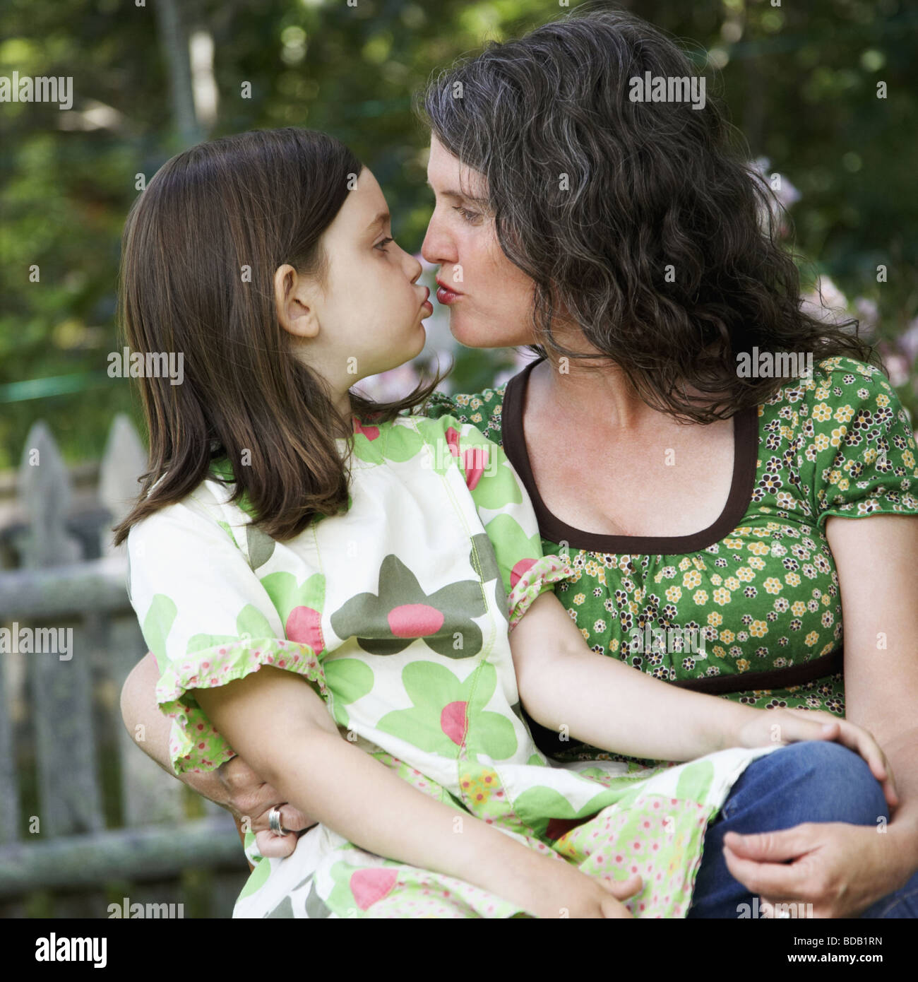 Mature woman with a girl kissing each other - Stock Image