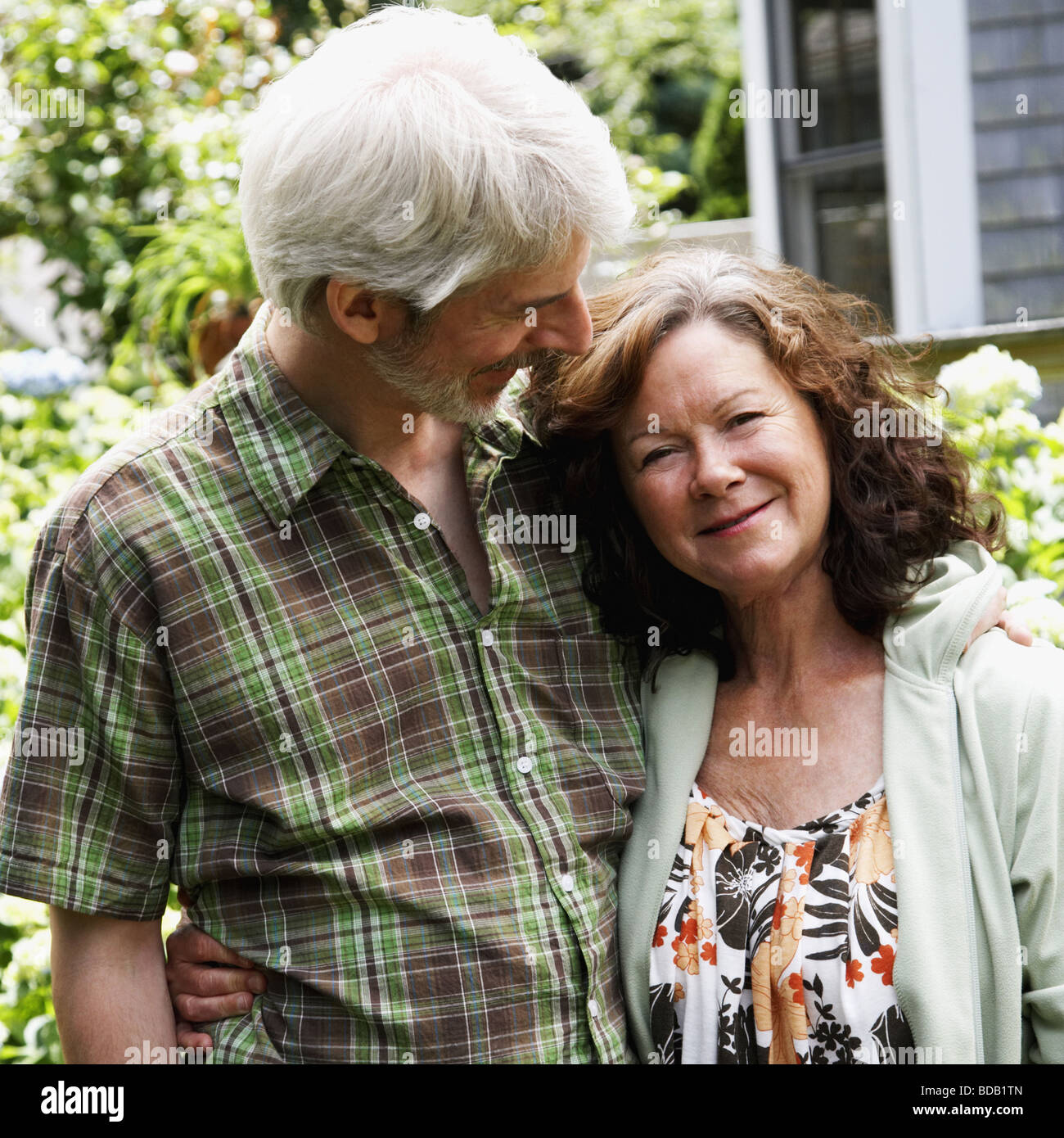 Mature couple smiling with arm around - Stock Image