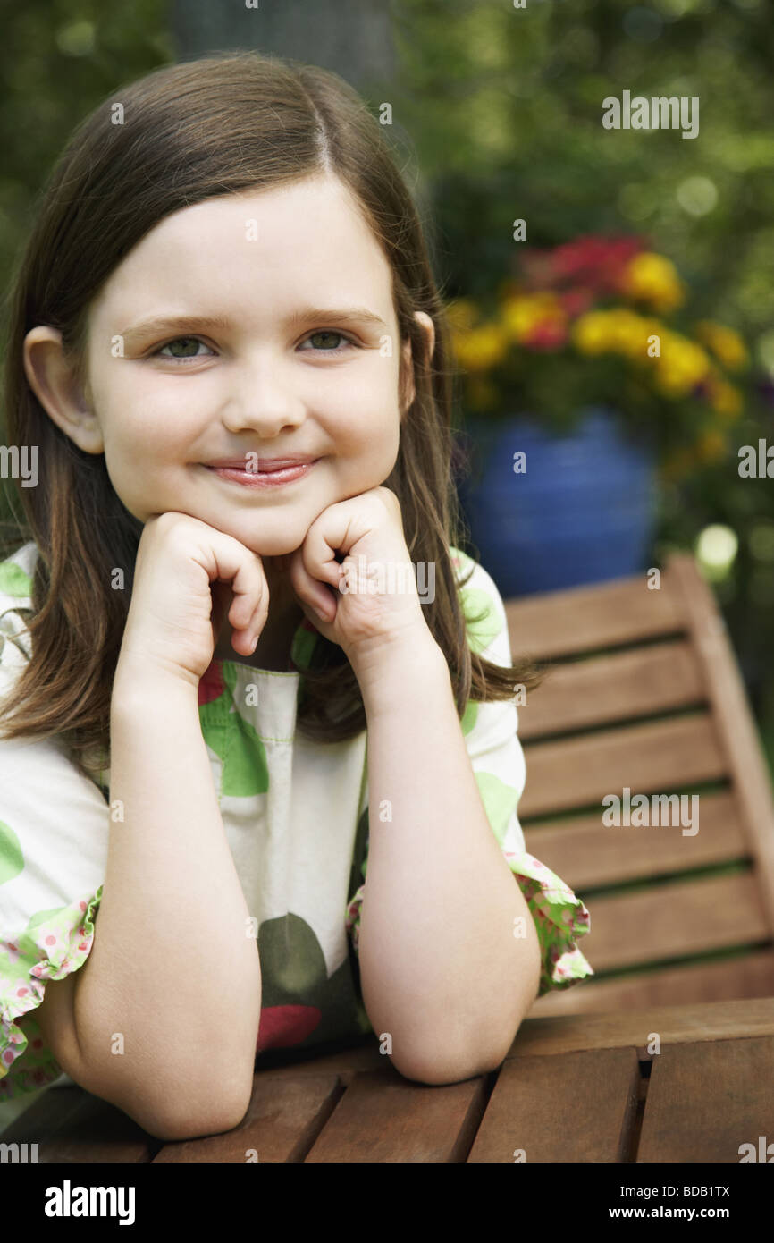 Girl leaning on her elbows and smiling - Stock Image