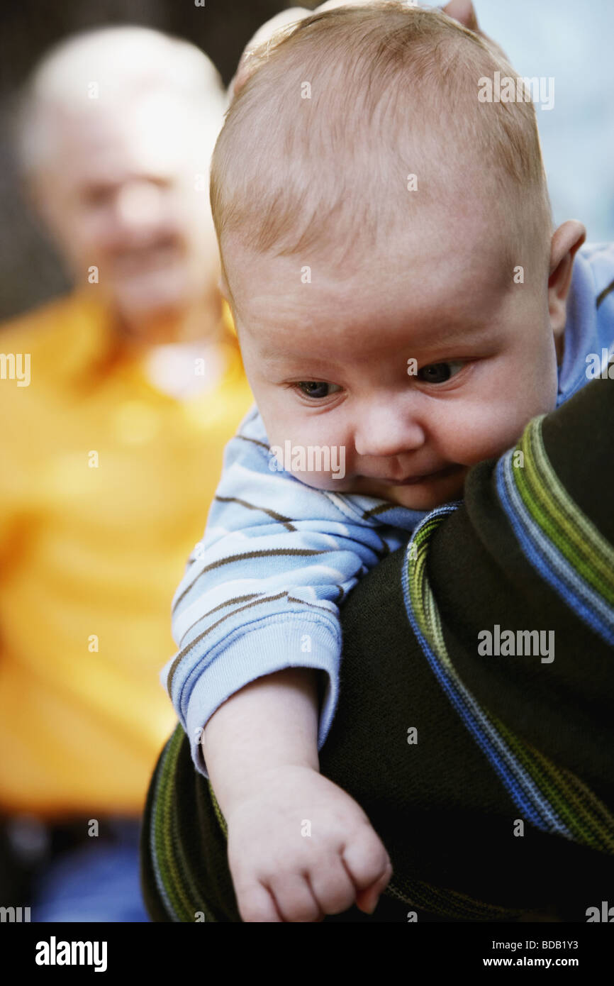 Close-up of a person carrying a baby - Stock Image