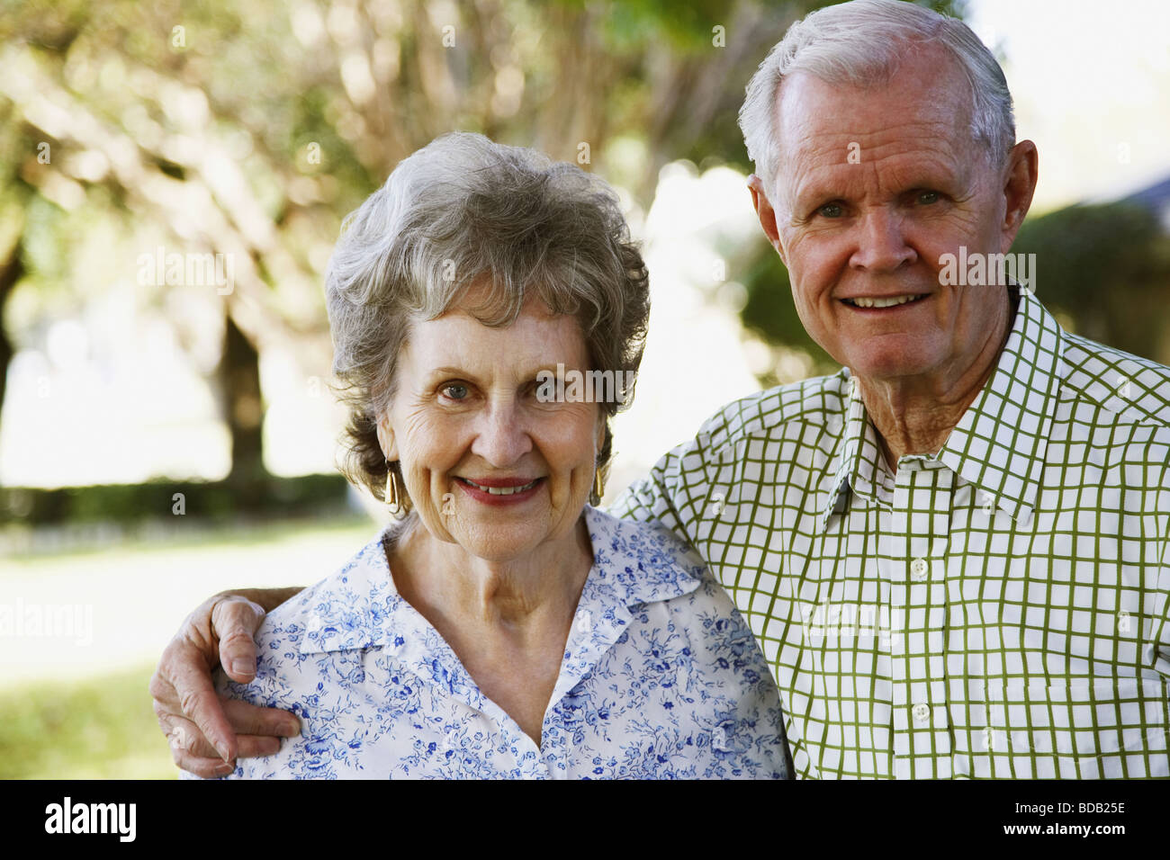 Portrait of a senior man with arm around a senior woman and smiling - Stock Image