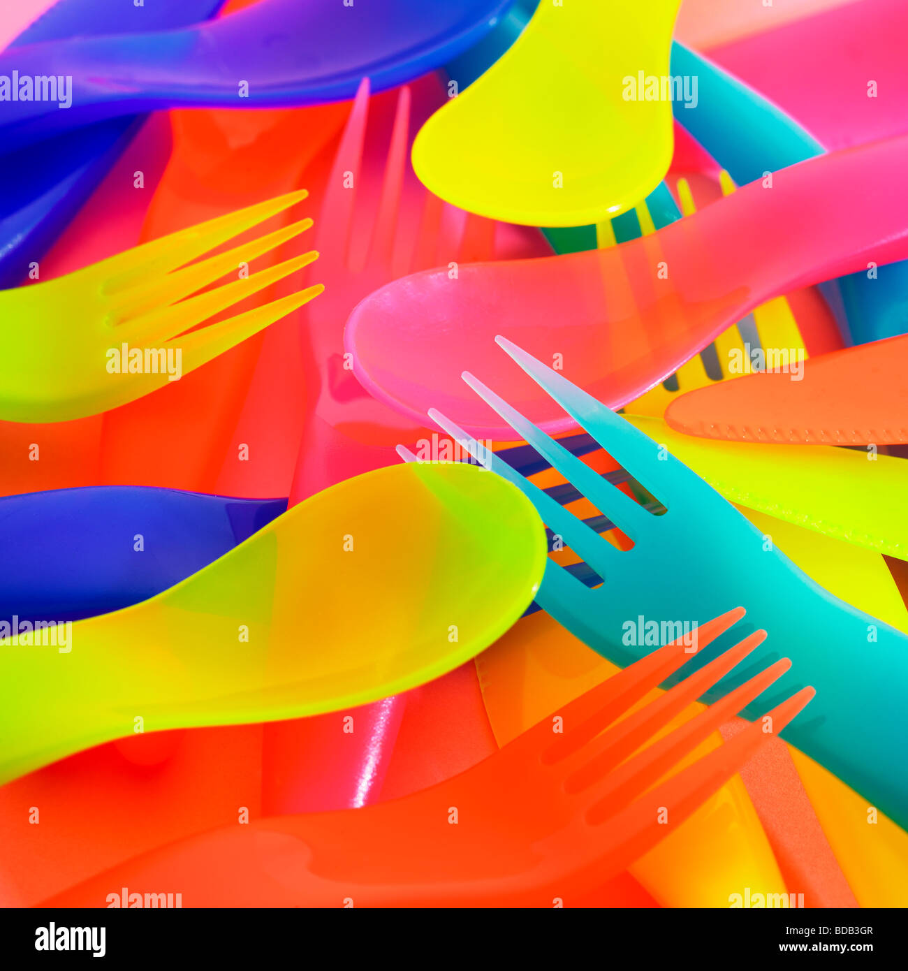 Brightly coloured plastic cutlery. - Stock Image