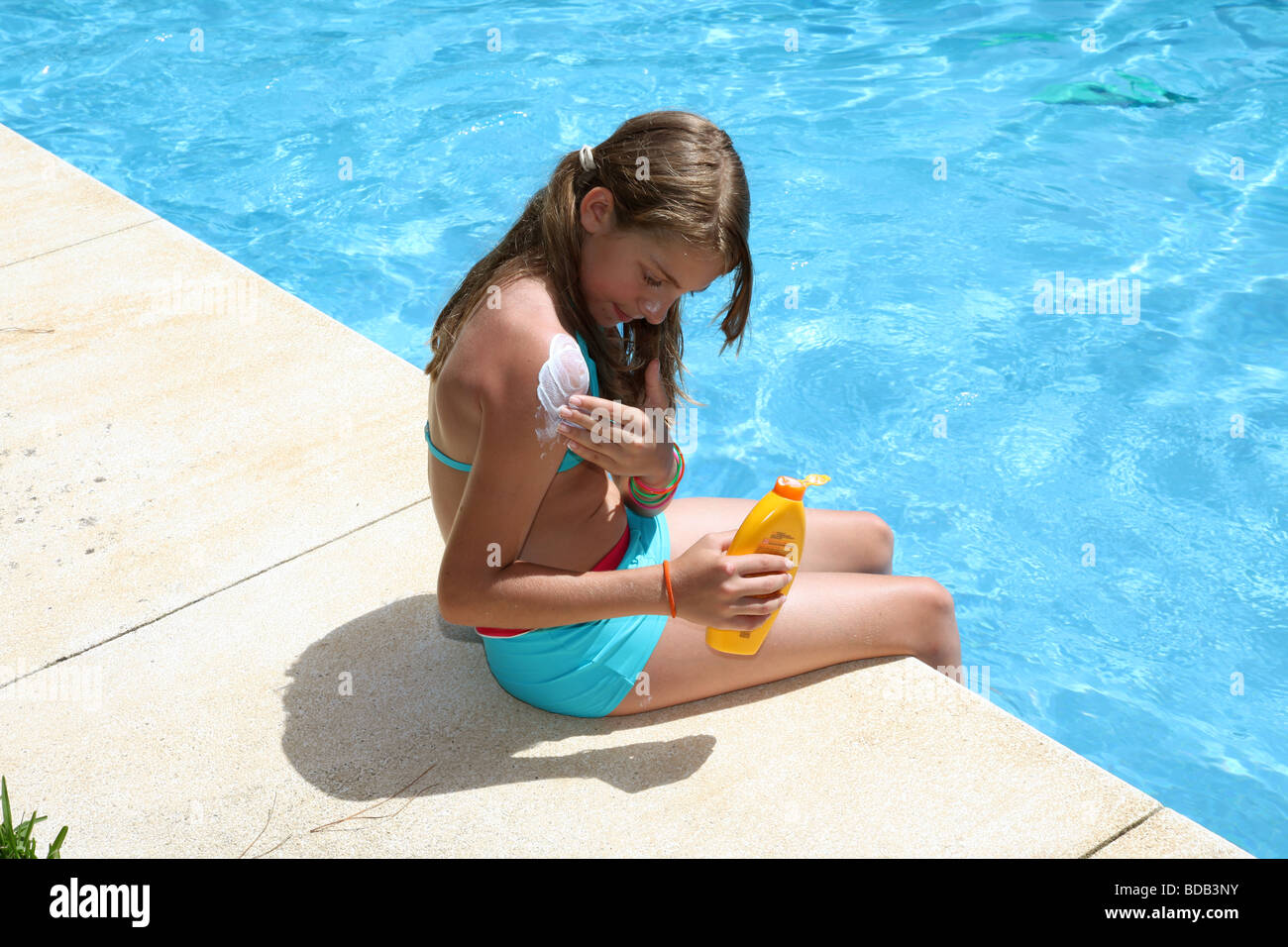 Young Caucasian girl applying suncream sitting by a pool - Stock Image