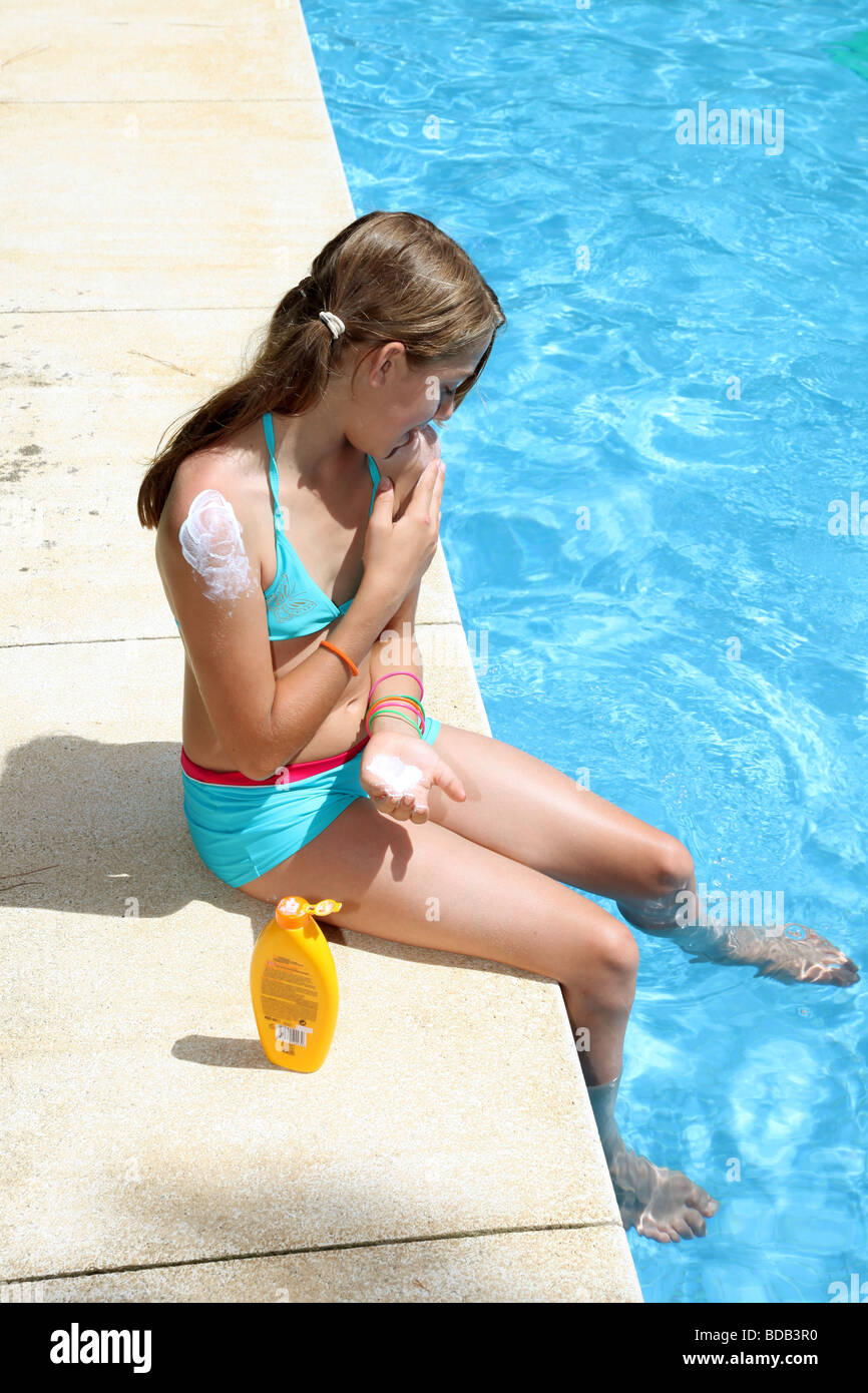 Young Caucasian girl applying suncream by the side of a pool - Stock Image