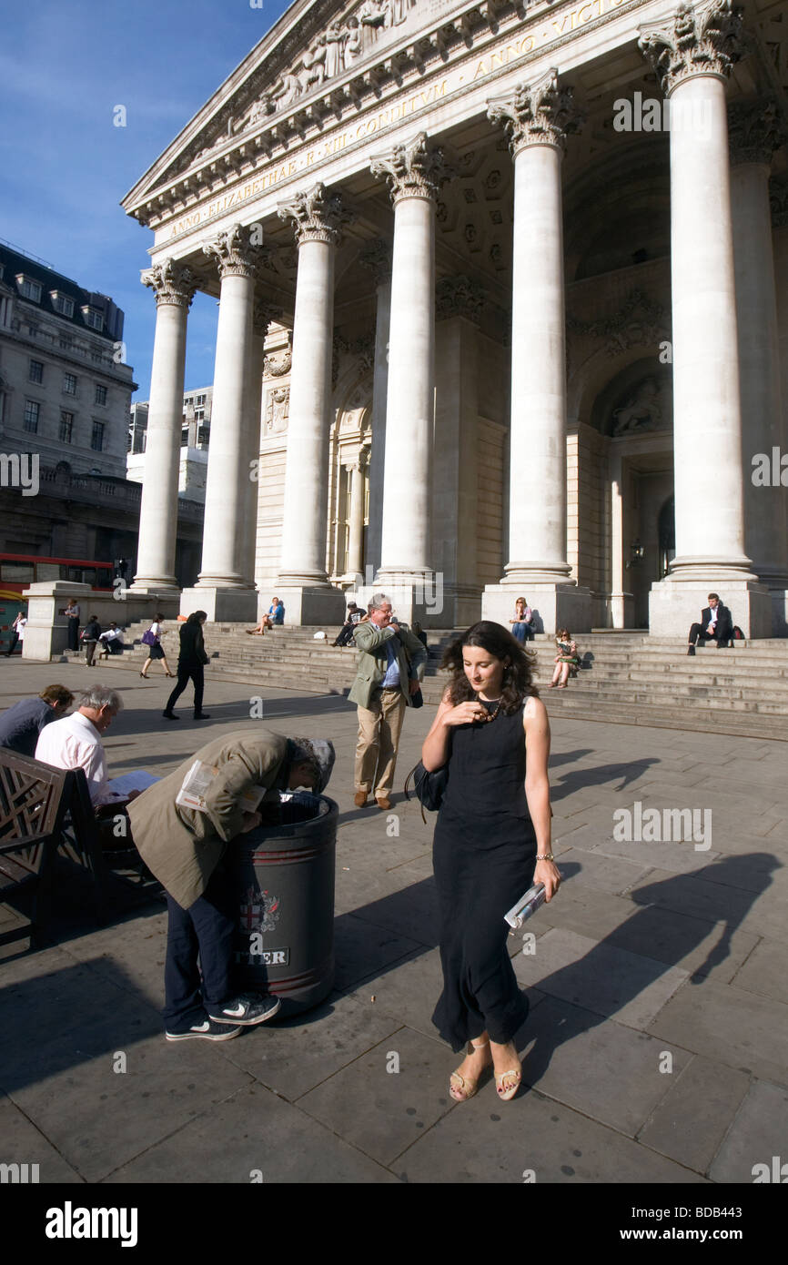 a man looking in a bin or trash can for food near the bank of england in the city of london Stock Photo