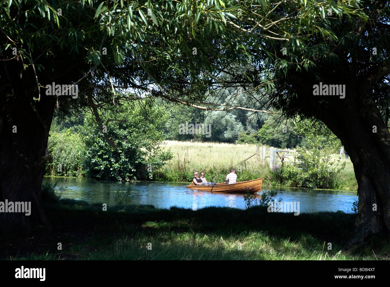 people Boating on the river Stour framed by trees Between The historic village of Dedham and Flatford in Constable Stock Photo