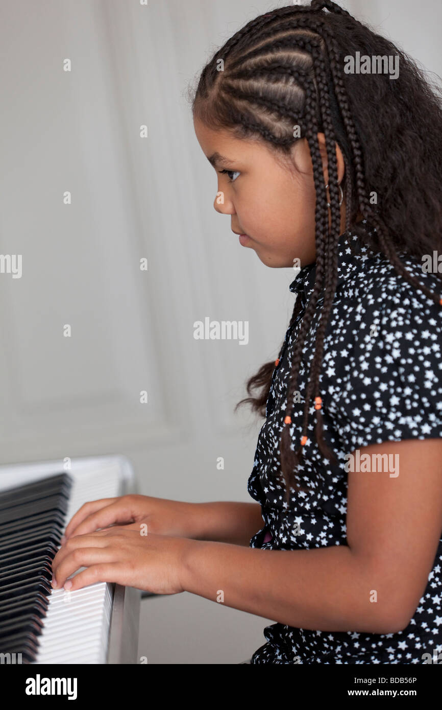 Little girl is playing the electric piano - Stock Image