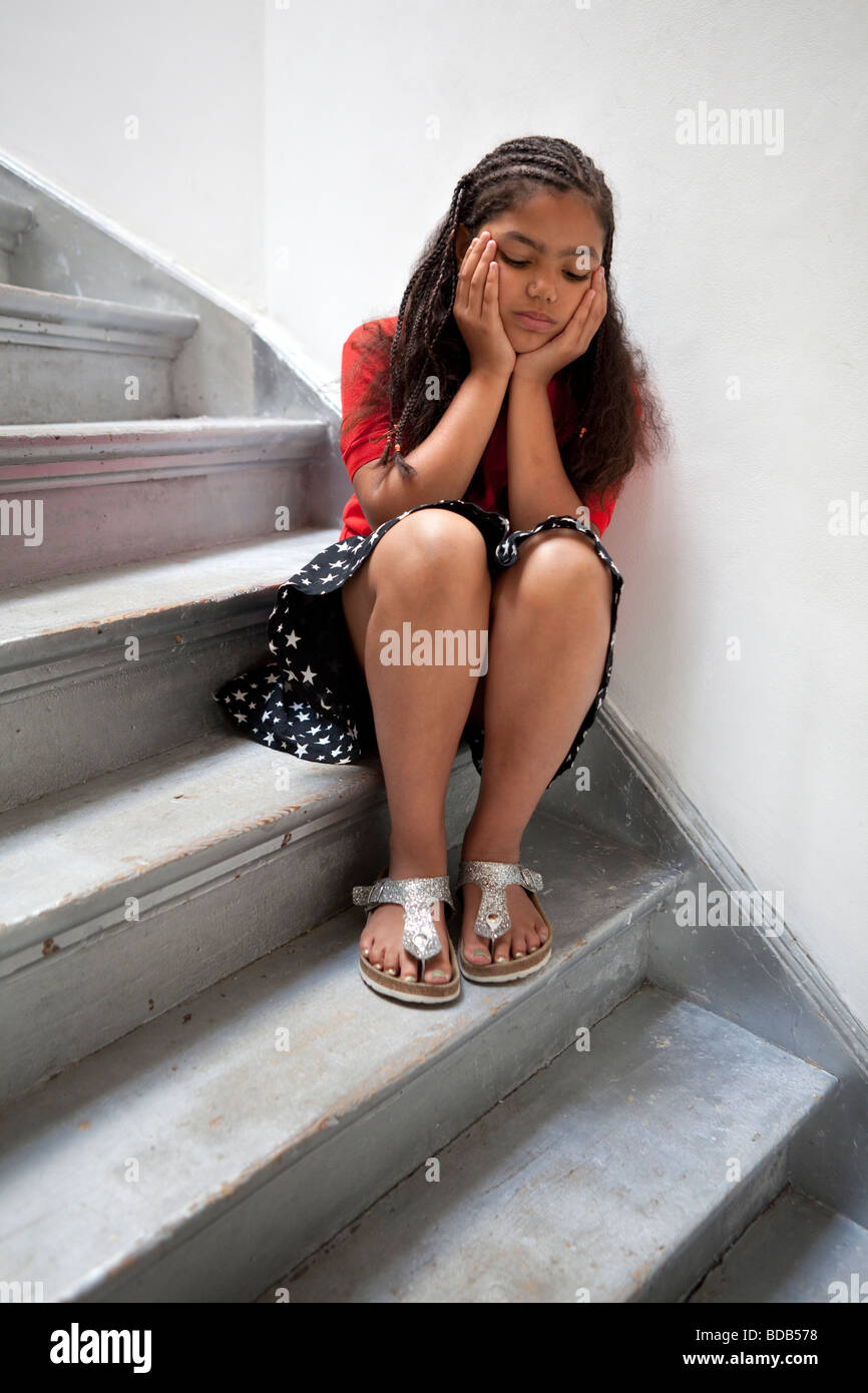 Sad girl sitting on the stairs - Stock Image