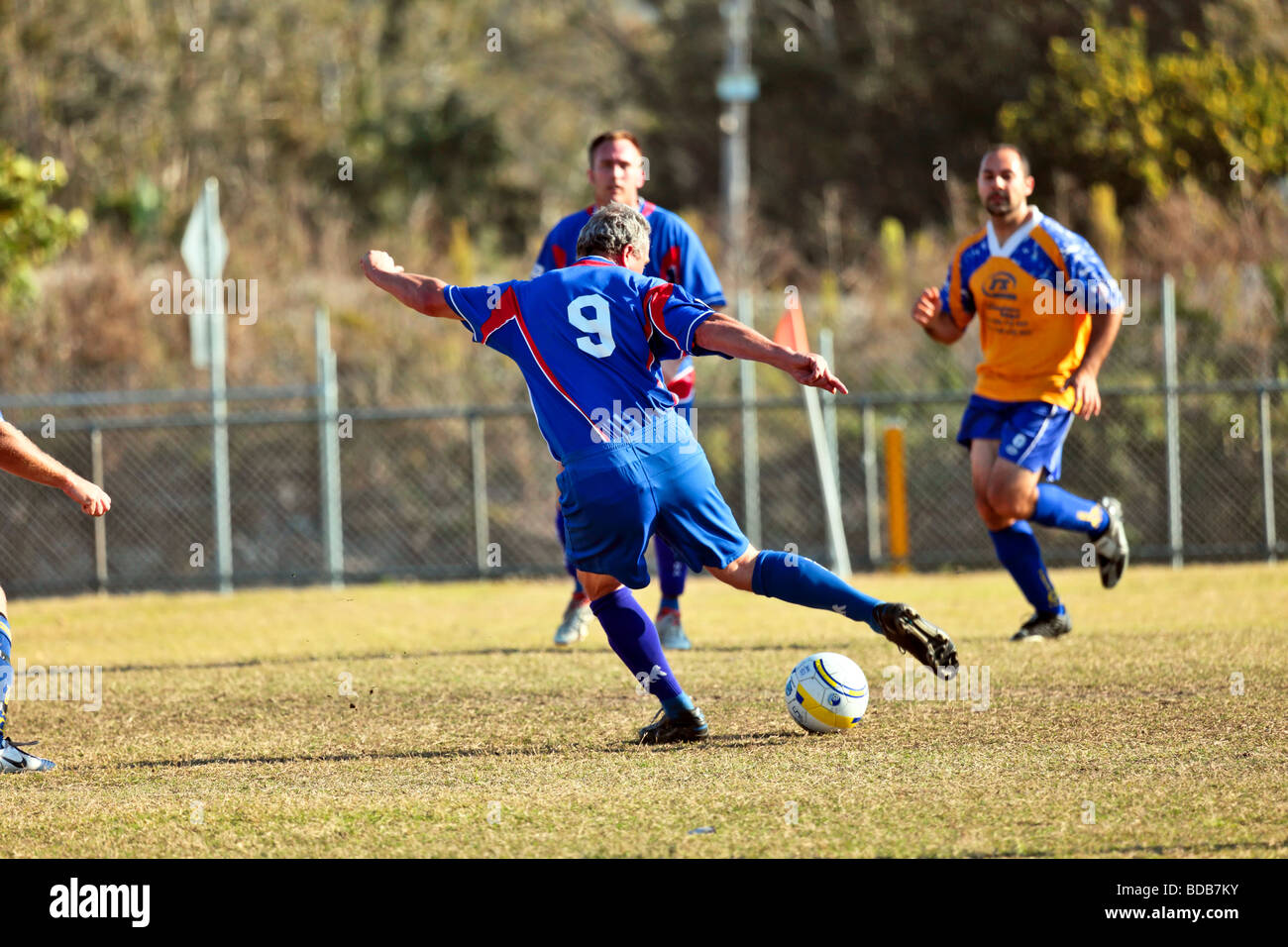 Two soccer teams playing a match heading the ball dribbling and kicking - Stock Image
