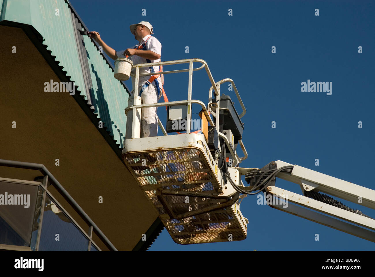 Painters working from a hydraulic boom, Queensland Australia - Stock Image