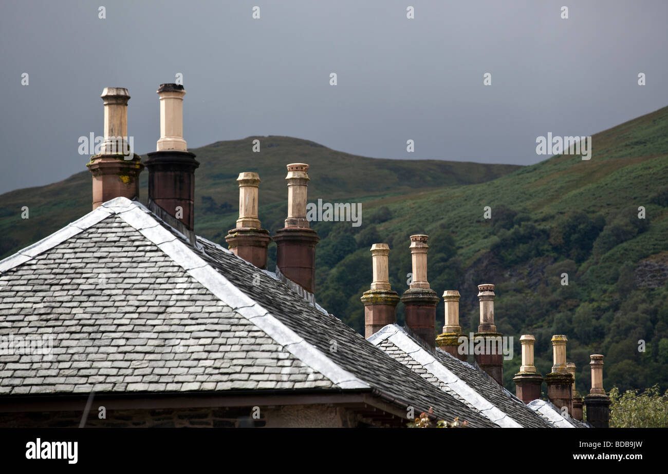 Rows of stone chimney pots in the Scottish village of Luss against the backdrop of nearby hills - Stock Image