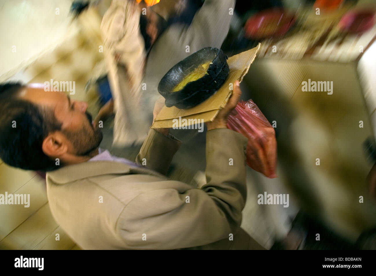 A waiter carries a Yemeni traditional stewed meat dish known as 'Salta' at Humayda Salta Restaurant located - Stock Image