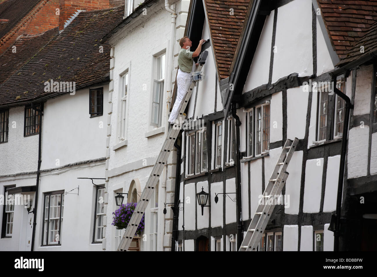 A painter at work on a house in Mill Street in Warwick UK - Stock Image