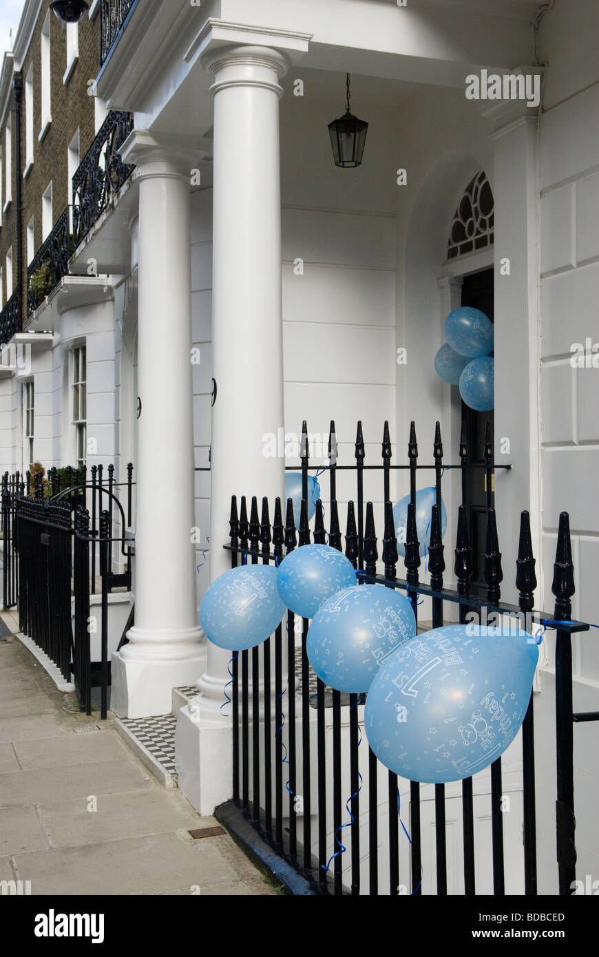Blue Balloons For A Baby Boys First Birthday Party Tied On Front Door And Railings Outside House London UK
