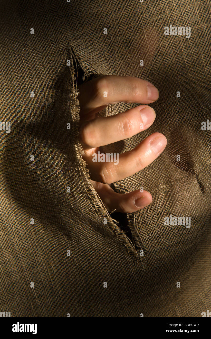 A hand breaks through. - Stock Image