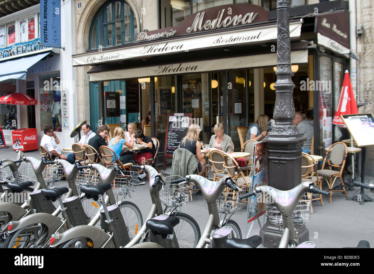 Paris free bicycle rent kiosk in front of Brasserie - Stock Image