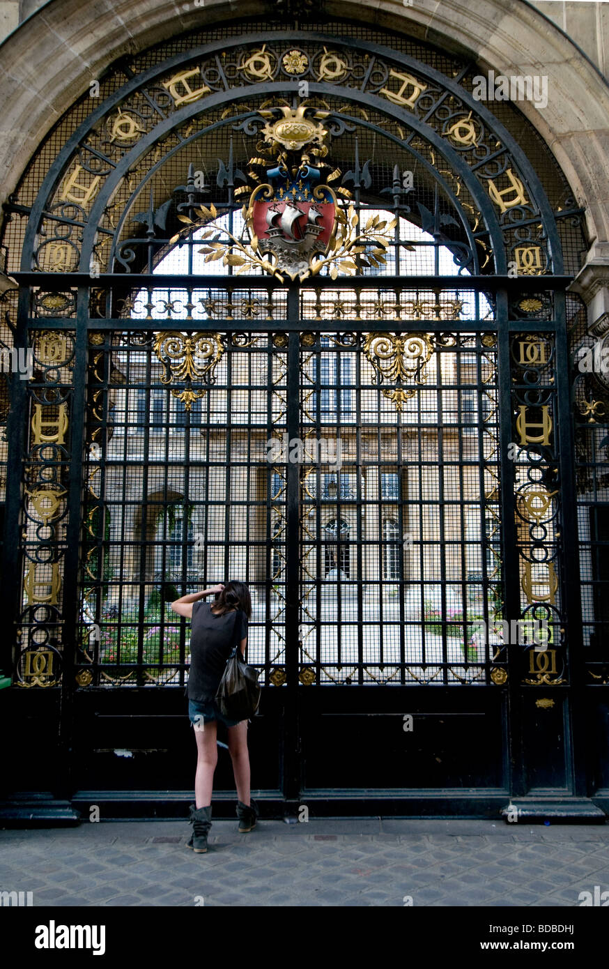 Girl trying to make a photo before gate with bars at Musee Carnavalet, Paris,  Le Marait - Stock Image