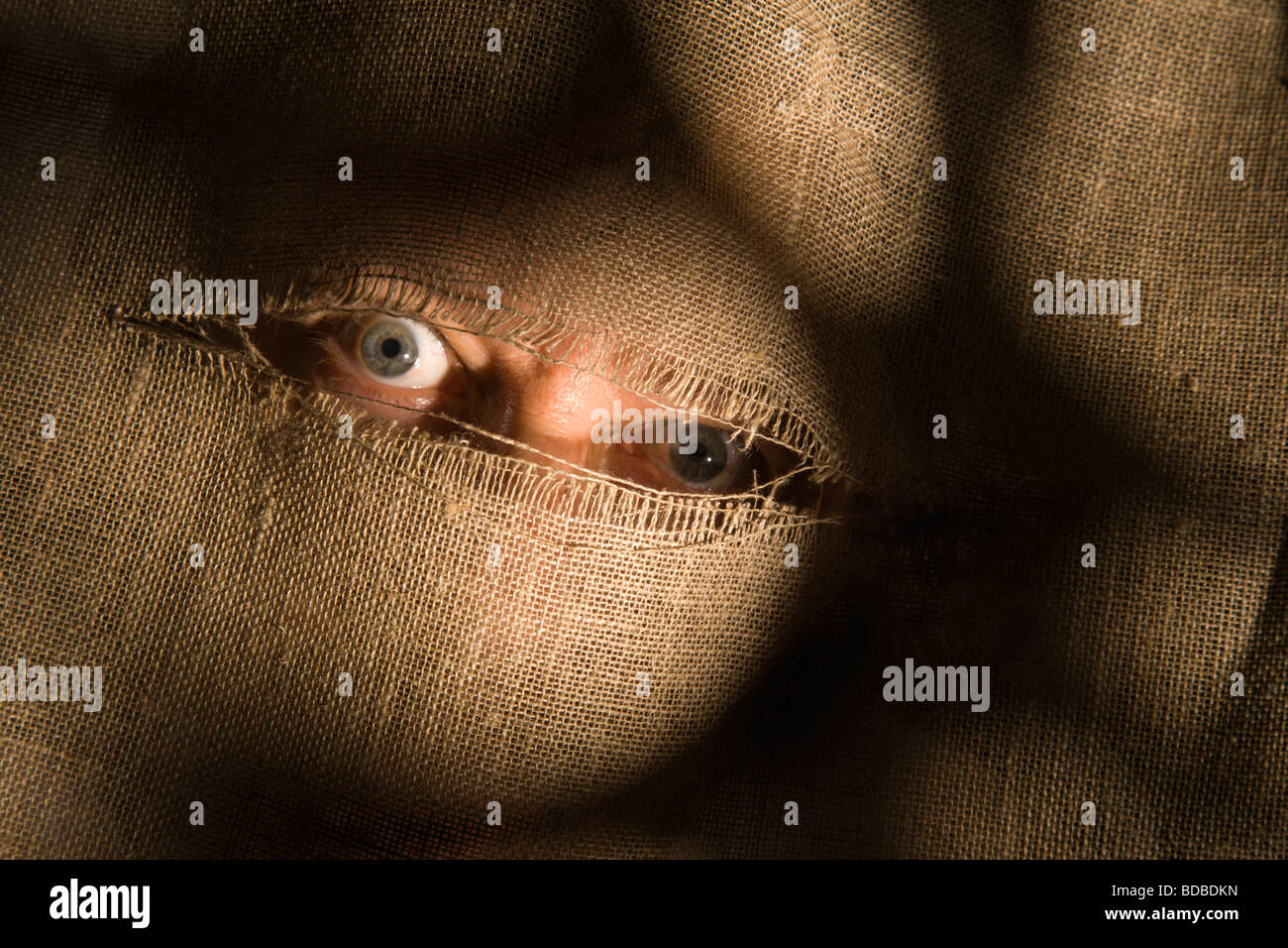 Menacing eyes stare through a slit torn the cloth. - Stock Image