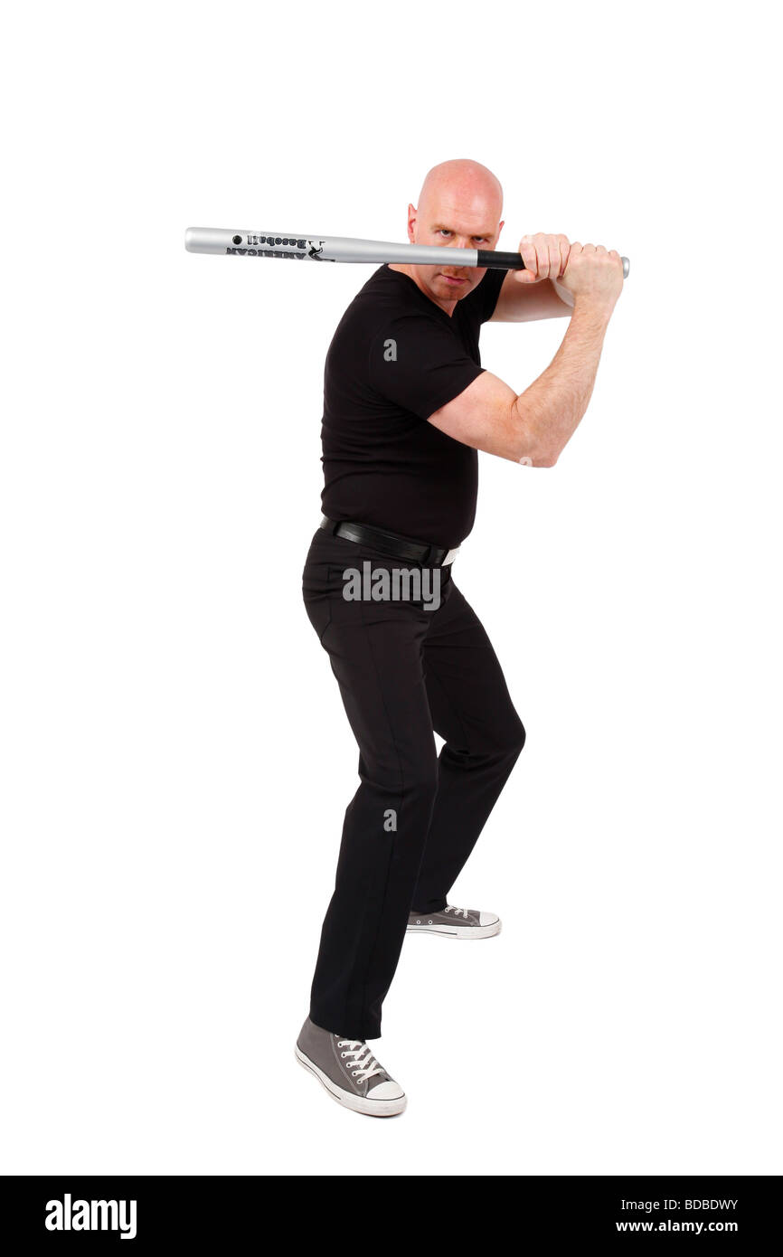bald headed man with baseball bat in front of his face is looking angry into the camera Stock Photo