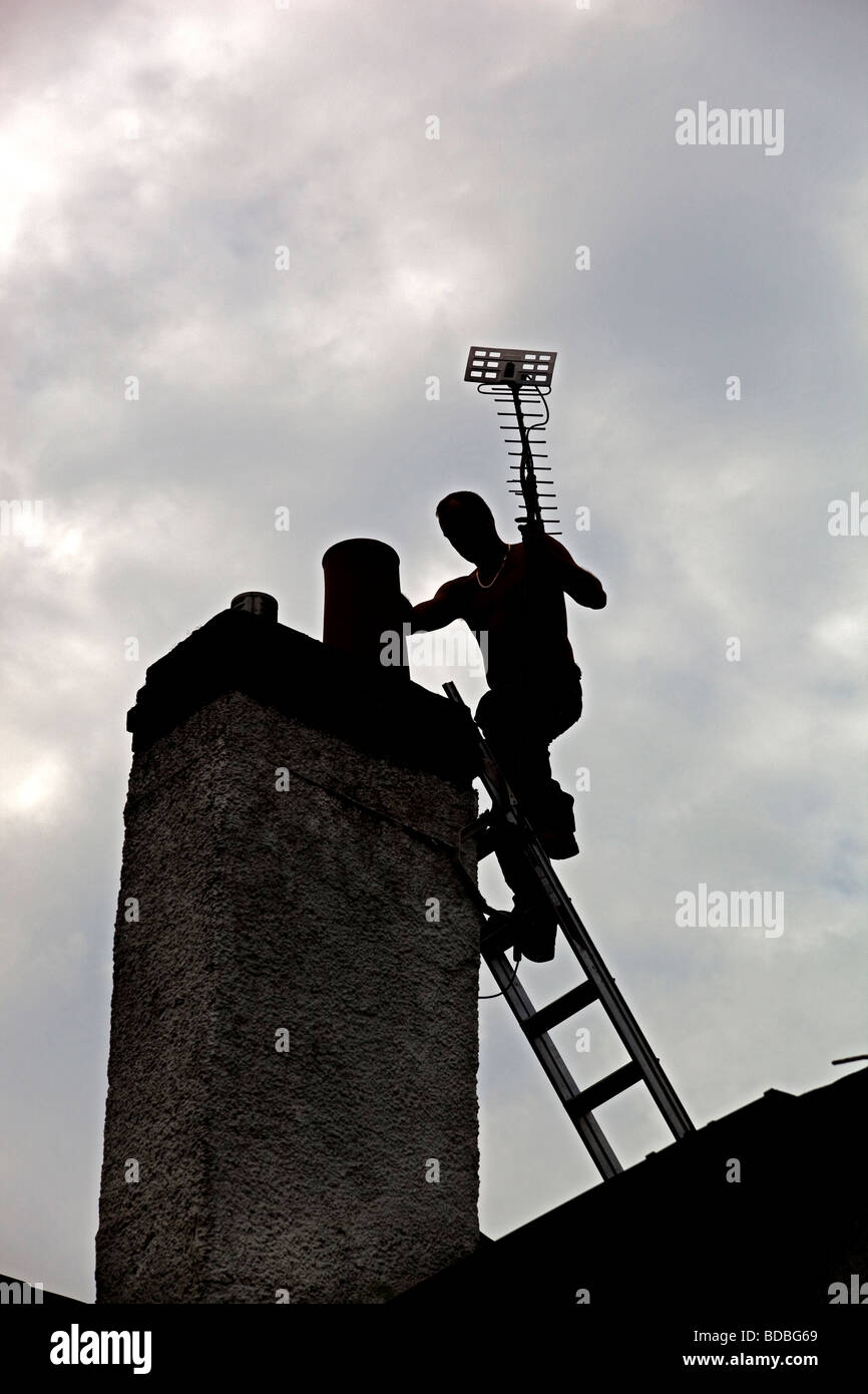 Builder on chimney sillhouette - Stock Image