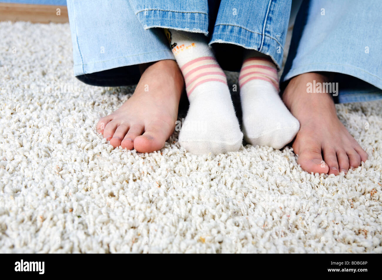 closeup of feet of mother and child sitting together on carpet
