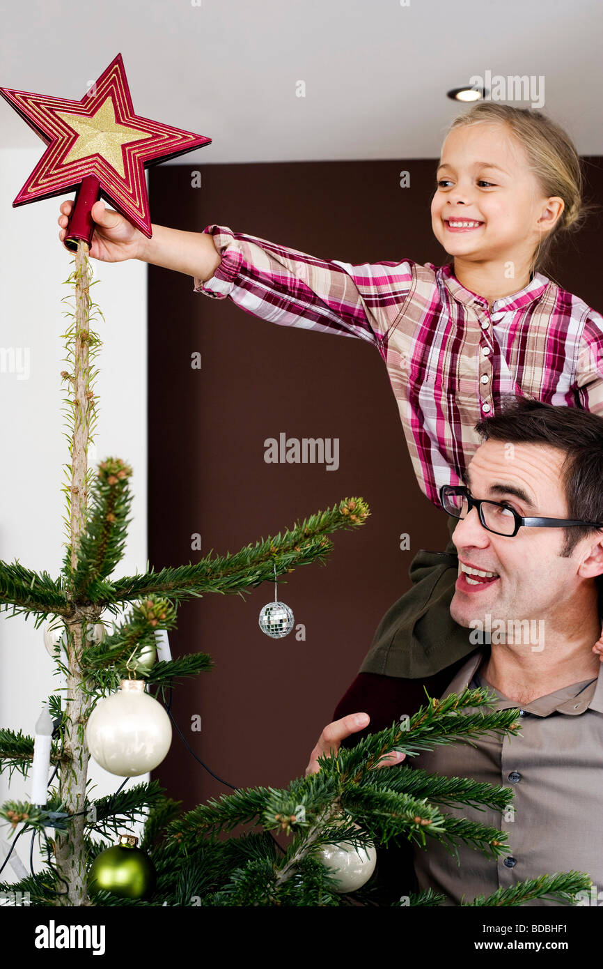 A Star For Christmas.Young Girl Putting Star On Top Of Christmas Tree Stock Photo