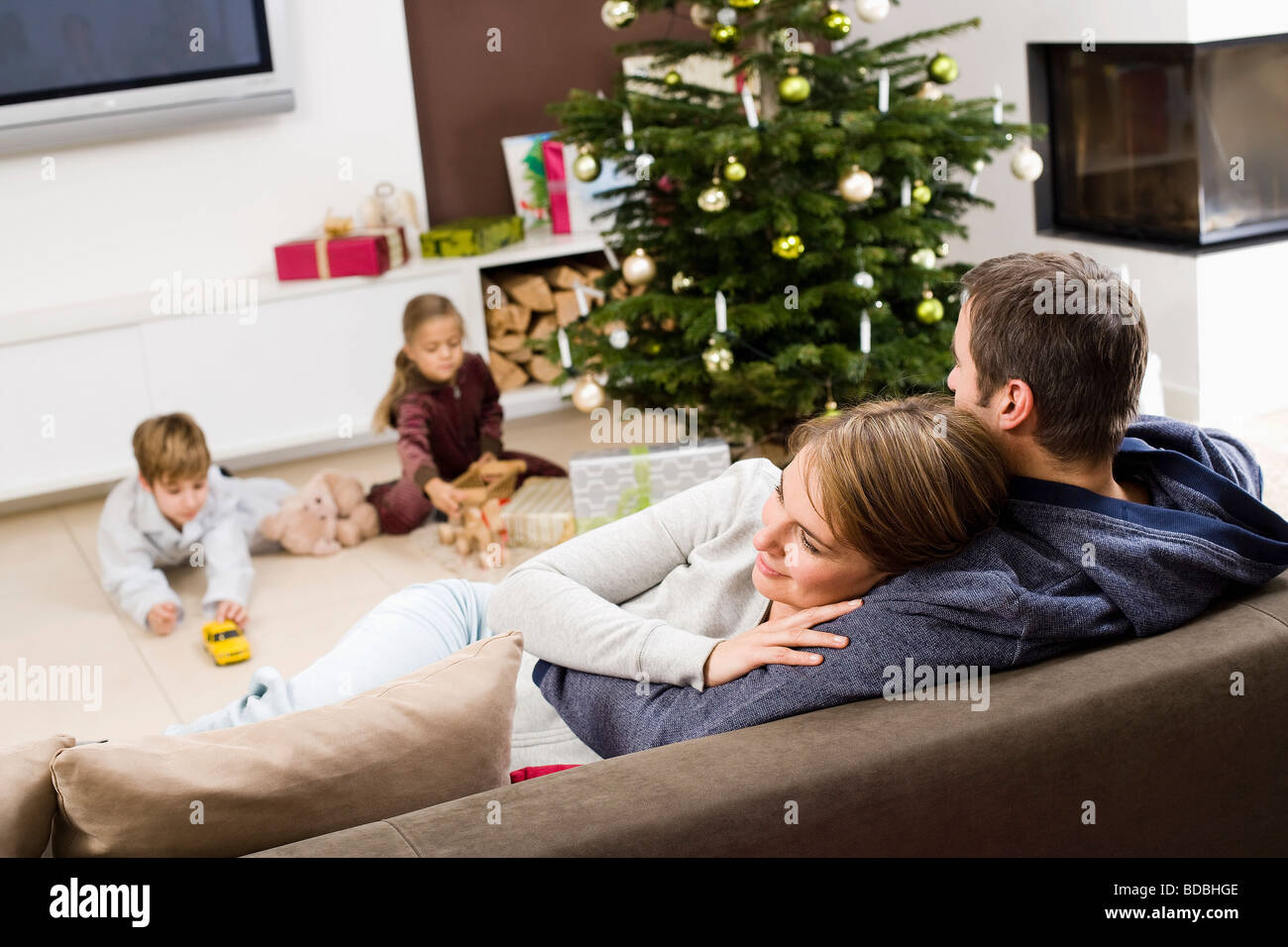 parents watching their children play on christmas morning - Stock Image