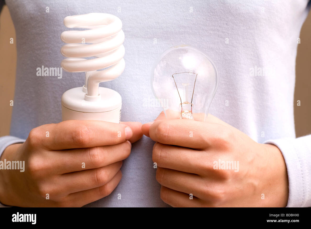 close-up of young woman holding conventional and low energy light bulb - Stock Image