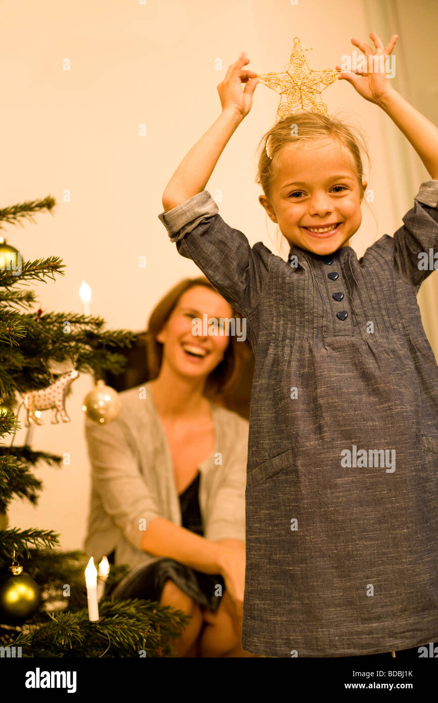 young girl making fun with star from christmas decoration - Stock Image