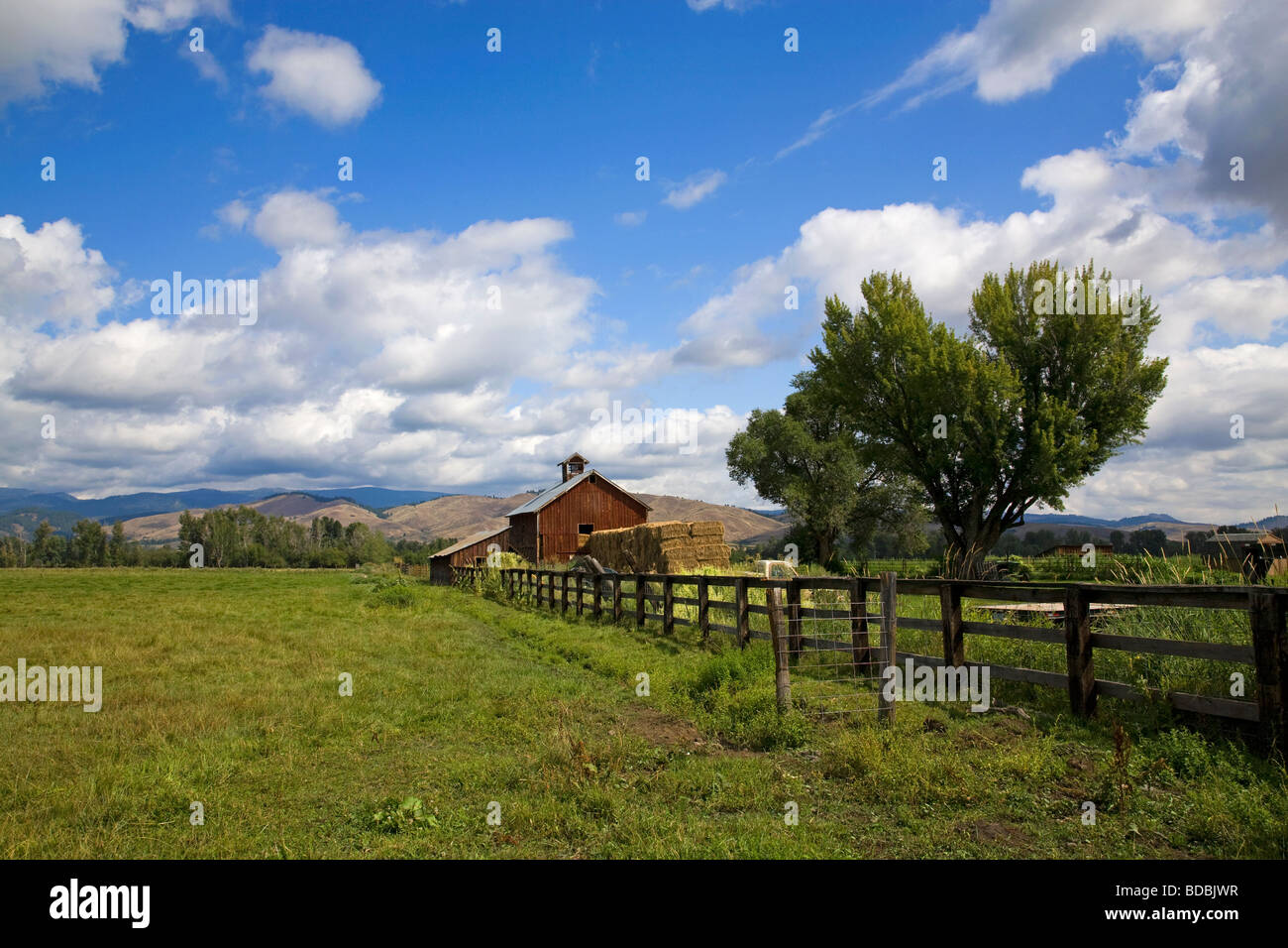 An old red barn and haystack on a ranch near Halfway Oregon on the slopes of the Wallowa Mountains in eastern Oregon - Stock Image
