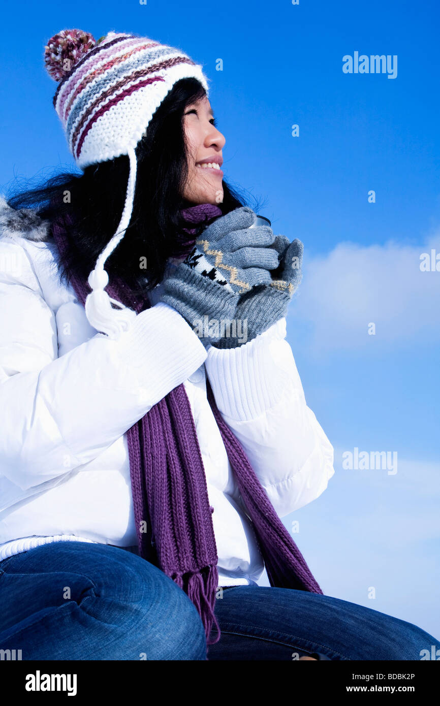 portrait of young asian woman in winter holding mug - Stock Image