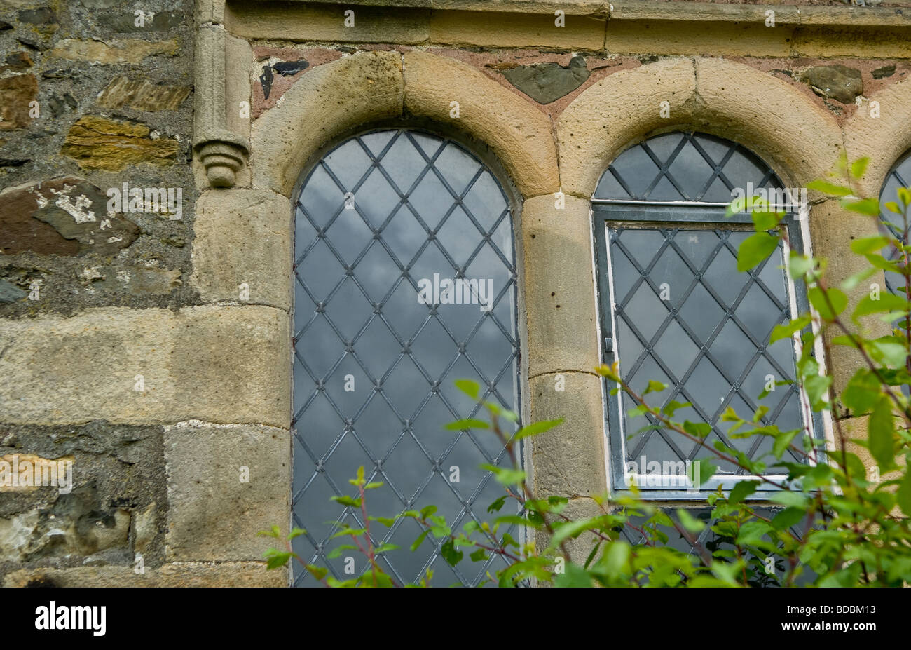 Stone arch leaded windows at the church in Hawkshead, Lake district, Cumbria - Stock Image