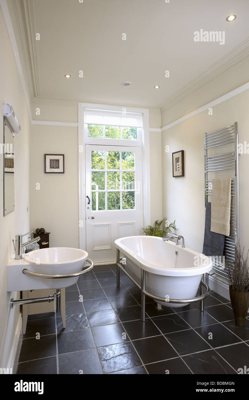 Modern roll-top bath in modern bathroom with slate flooring and ...