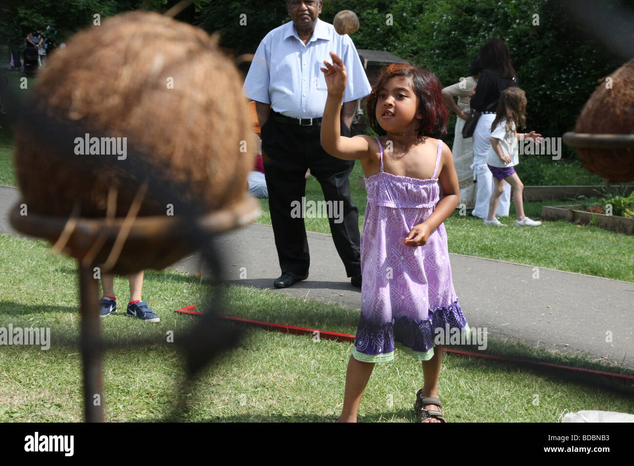 A girl aims to knock coconuts off their perch at a coconut shy at a school fete - Stock Image