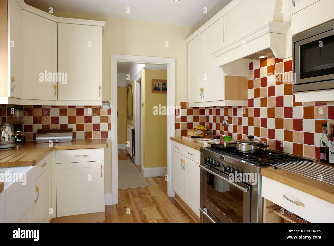 Brown and cream wall tiles in traditional cream kitchen with range ...
