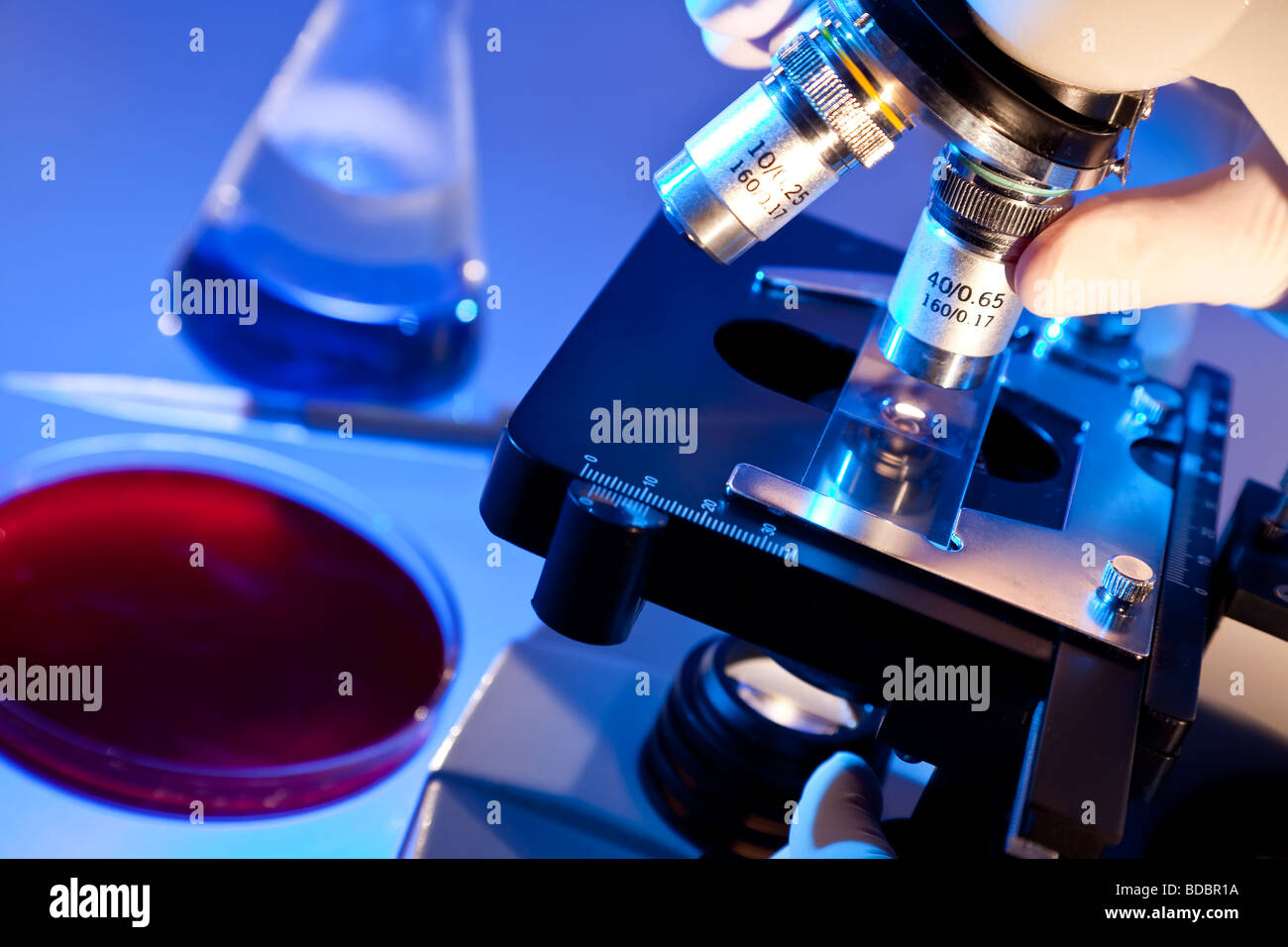 A medical or scientific researcher using a microscope in a laboratory environment with conical flask pipette and - Stock Image