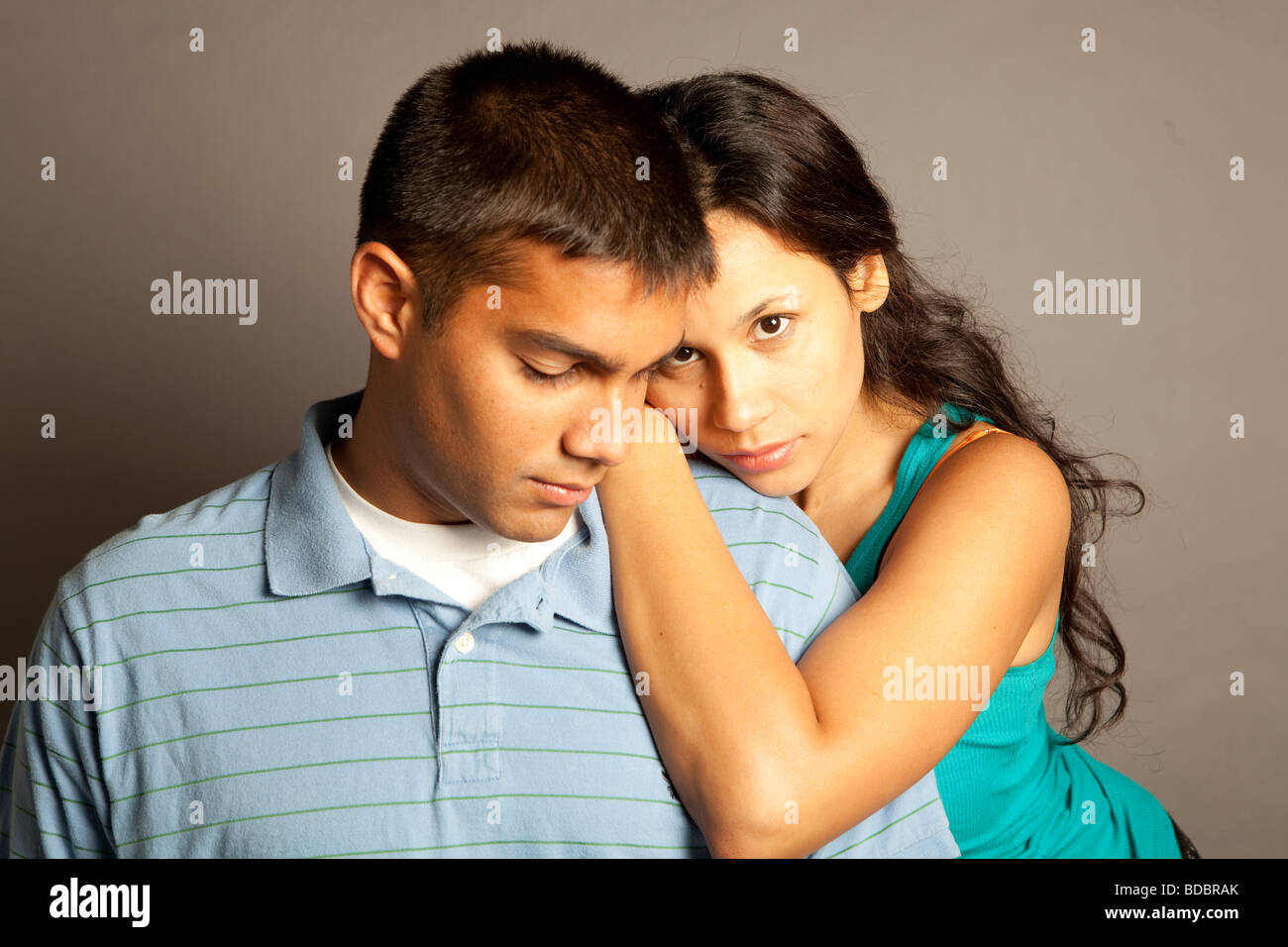 Male female couple posing together in studio in front of a neutral colored backdrop.  Woman is resting hands on - Stock Image