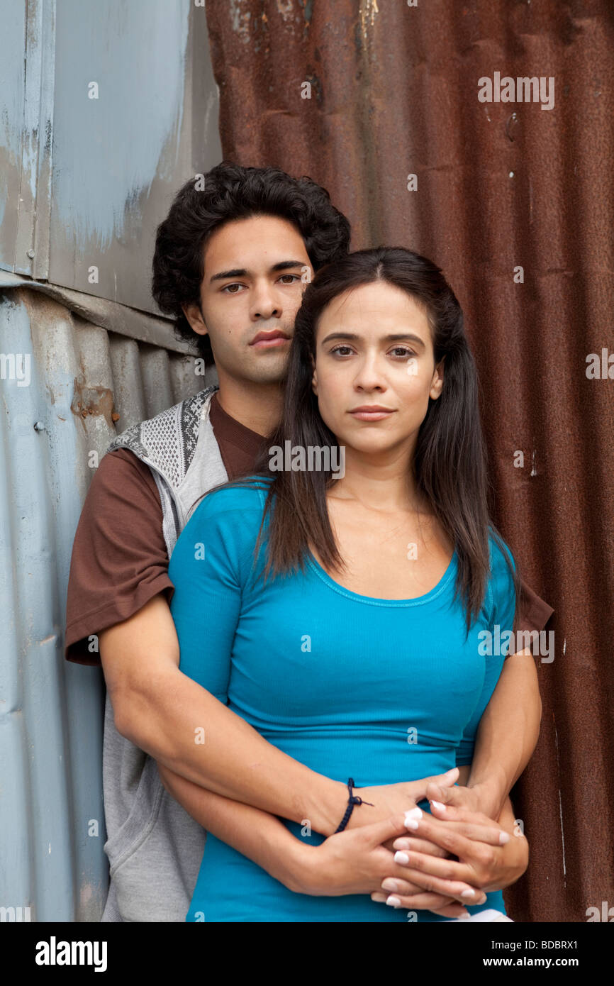 Hispanic Latino male and female couple hugging, looking at camera in urban alley setting. - Stock Image