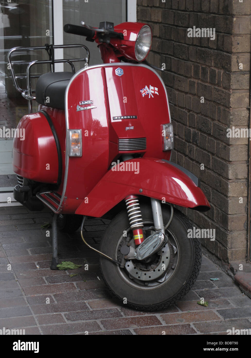 Red vespa px200 scooter by Piaggio parked in doorway in UK