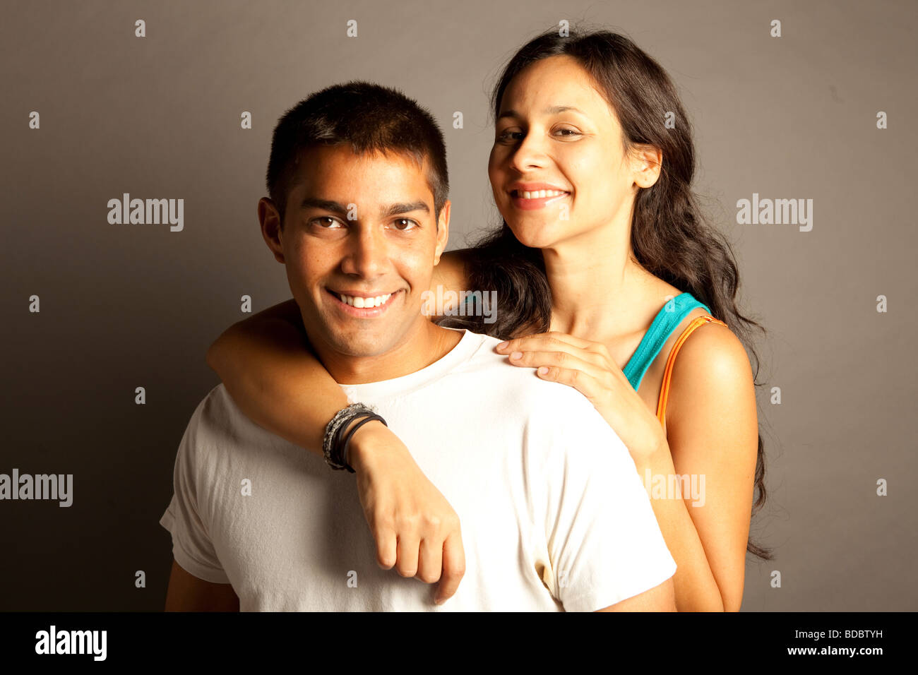 Male female couple posing together in studio in front of a neutral colored seamless. - Stock Image