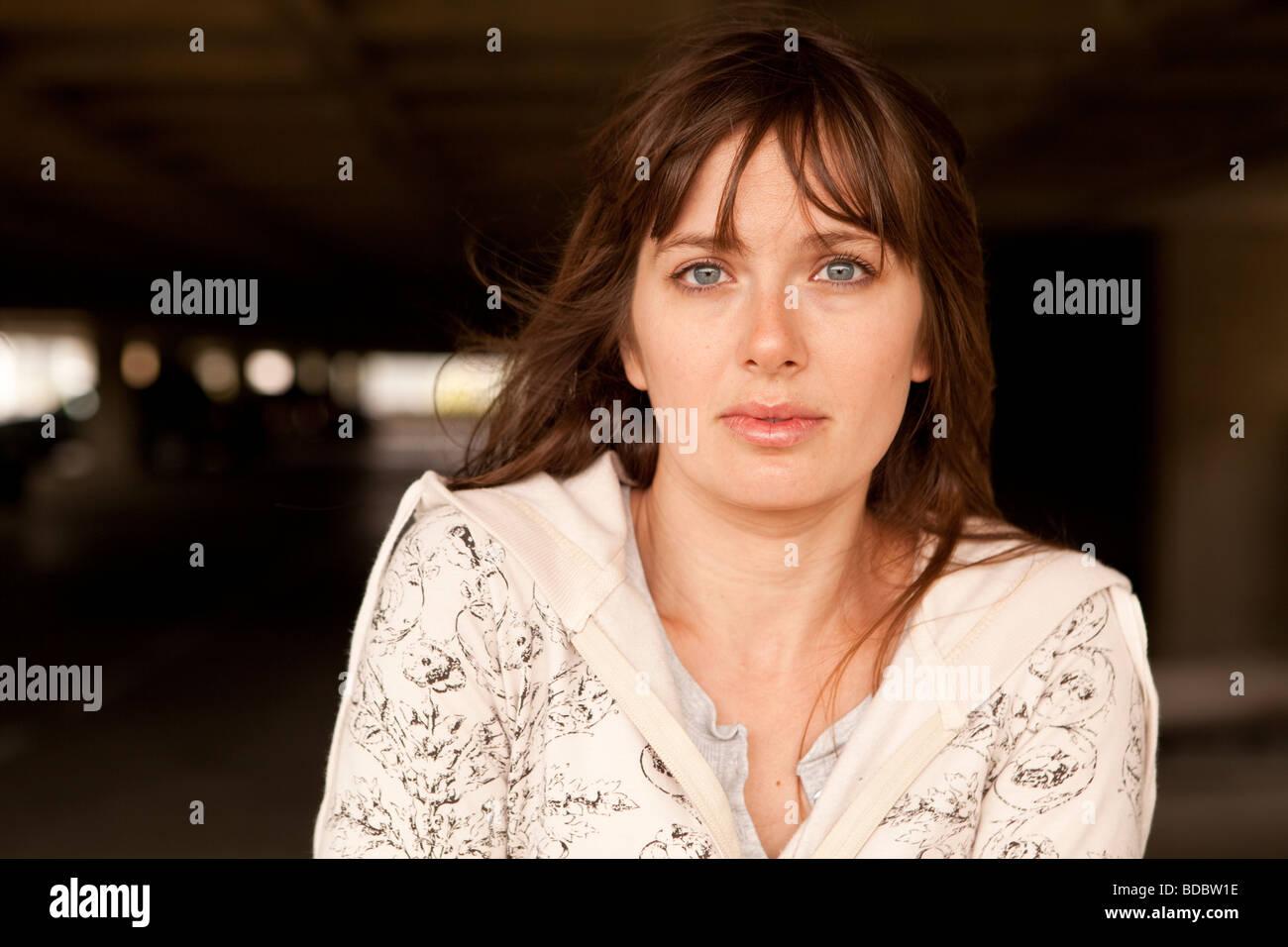 Portrait of Caucasian female brunette against waffle-like pattern of parking garage structure. - Stock Image
