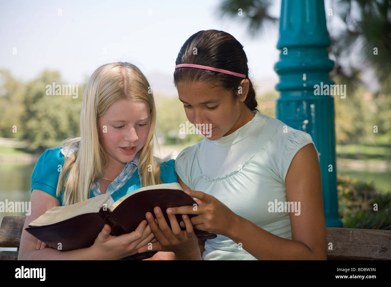 two 2 girls reading Racially mixed Ethnic diversity Hispanic Caucasian discuss Bible nature natural young person Stock Photo