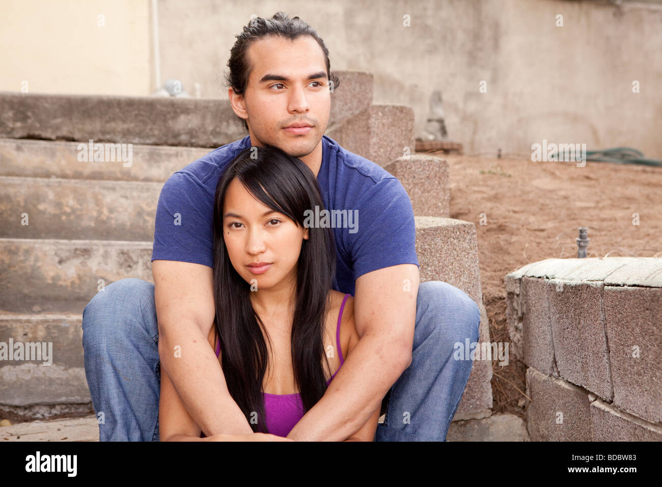Male and female couple sitting on concrete steps, his arms are around her.  Looking at camera.  Woman is Filipino. - Stock Image