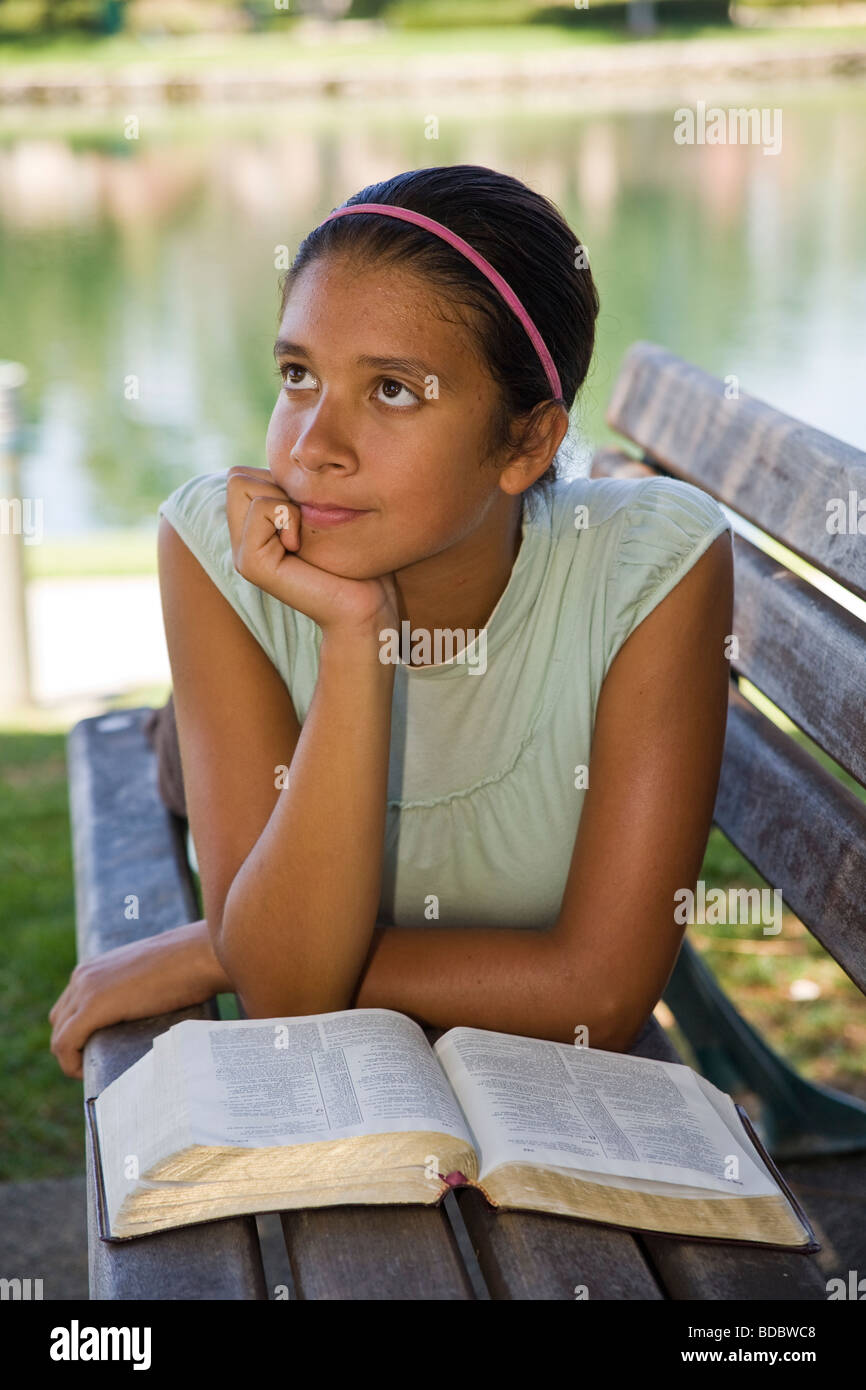 Junior high Hispanic/Caucasian girl reflecting on God's Word. MRMyrleen Pearson - Stock Image